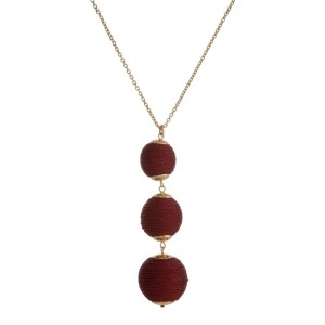 """Gold tone necklace with three, metallic burgundy thread wrapped beads. Approximately 30"""" in length."""