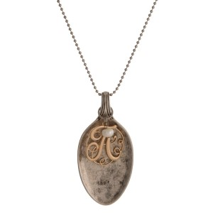 """Silver tone necklace with a spoon pendant and a two tone, initial charm. Approximately 30"""" in length."""