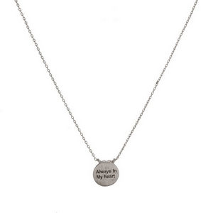 """Dainty metal necklace with a circle pendant, stamped with """"Always in My Heart."""" Approximately 16"""" in length."""