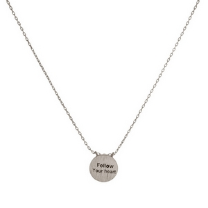"Dainty metal necklace with a circle pendant, stamped with ""Follow Your Heart."" Approximately 16"" in length."
