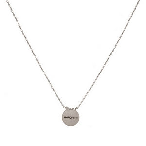 "Dainty metal necklace with a circle pendant stamped with an arrow and ""Hope."" Approximately 16"" in length."