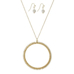 """Long, metal necklace set with a pearl beaded circle pendant and matching fishhook earrings. Approximately 30"""" in length."""