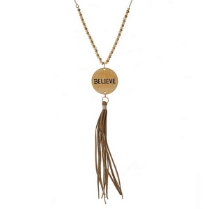 "Dainty necklace with a coin pendant, stamped with ""Believe"" and accented by a faux leather tassel. Approximately 32"" in length."