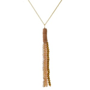 "Gold tone necklace with a wooden, faceted, and natural stone beaded tassel pendant with suede wrapping accents. Approximately 32"" in length."