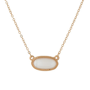 "Dainty, gold tone necklace with an oval shaped, faceted stone pendant. Approximately 16"" in length."