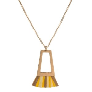 """Gold tone necklace with a hammered, open square shape and ombre raffia tassel. Approximately 32"""" in length."""