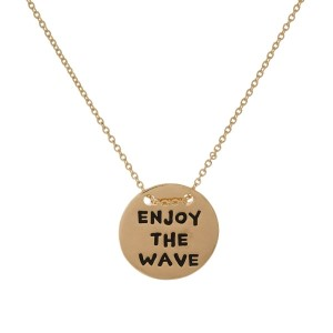 """Dainty metal necklace with a circle pendant stamped with """"Enjoy The Wave."""" Approximately 16"""" in length."""