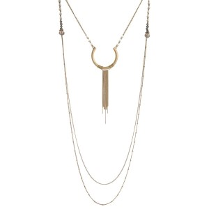 """Gold tone, two layer necklace with a horn and tassel pendant and beaded accents. Approximately 22"""" and 40"""" in length."""