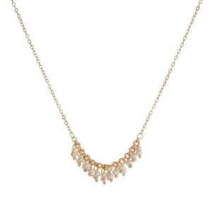 """Dainty gold tone necklace with a beaded fringe pendant. Approximately 16"""" in length."""