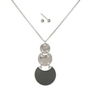 """Dainty silver tone necklace with a faux leather circle pendant and matching earrings. Approximately 16"""" in length."""
