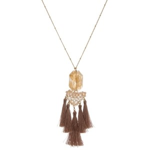 "Gold tone necklace with a natural stone pendant, beaded accents and tassels. Approximately 32"" in length."