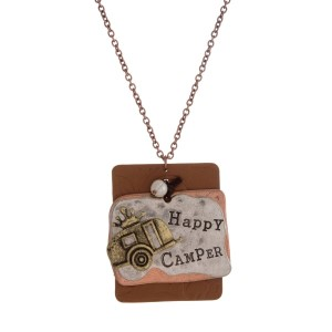 """Long, metal necklace with a """"Happy Camper"""" stamped metal and leather pendant. Approximately 30"""" in length."""