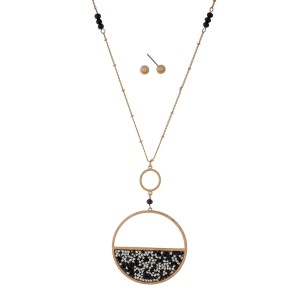 """Long, metal necklace set with a rhinestone, circle pendant and matching fishhook earrings. Approximately 30"""" in length."""