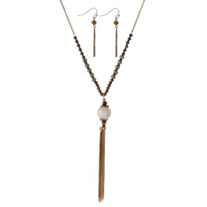 "Long necklace with faceted beads, pearl pendant and metal tassel. Approximately 26"" in length."