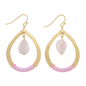 "Matte gold tone fishhook earrings featuring a pale pink stone hanging from an open teardrop shape casting wrapped with pink thread. Approximately 1 1/2"" in length."