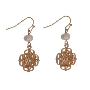 """Gold tone fishhook earrings with a clover and rhinestone charm and freshwater pearl bead. Approximately 1"""" in length."""