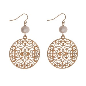 """Gold tone fishhook earrings with a filigree circle shape and a freshwater pearl bead. Approximately 2"""" in length."""