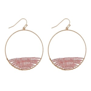 "Gold tone, circle, fishhook earrings with pink beading. Approximately 2"" in diameter."