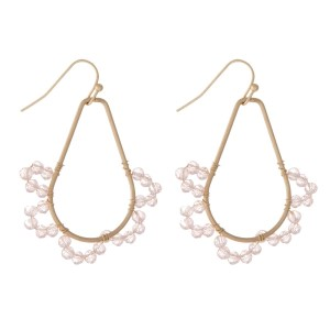 "Gold tone fishhook earrings with a teardrop shaped and a pink beaded scalloped design. Approximately 1.5"" in length."