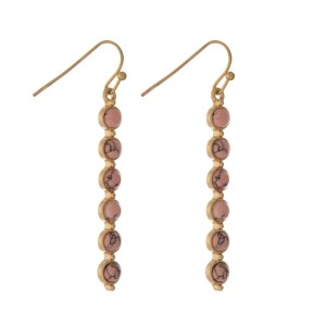 "Gold tone fishhook earrings with pink circle stones. Approximately 2"" in length."
