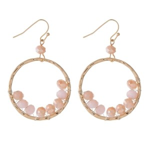 "Gold tone fishhook earrings with a hammered circle shape and wire wrapped blush pink beads. Approximately 1.25"" in diameter."
