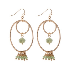 "Gold tone fishhook earrings with an open oval shape and light green faceted beads. Approximately 2"" in length."