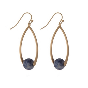"Matte gold tone fishhook earrings with an oval shape and a blue natural stone bead. Approximately 1.5"" in length."