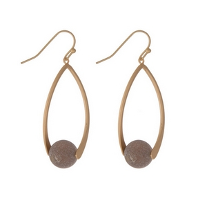 "Matte gold tone fishhook earrings with an oval shape and a gray natural stone bead. Approximately 1.5"" in length."