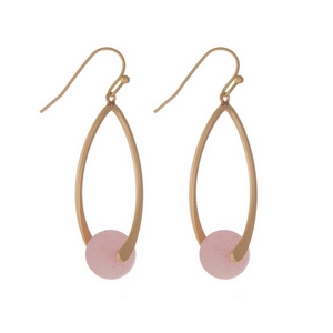 "Matte gold tone fishhook earrings with an oval shape and a pale pink natural stone bead. Approximately 1.5"" in length."