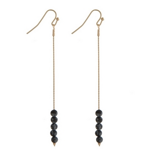 "Gold tone fishhook earrings with black natural stone beads. Approximately 3"" in length."