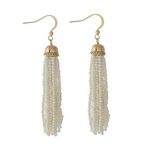 """Gold tone fishhook earrings featuring a white beaded tassel. Approximately 3"""" in length."""