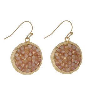 "Gold tone fishhook earrings featuring a peach beaded circle. Approximately 1"" in diameter."