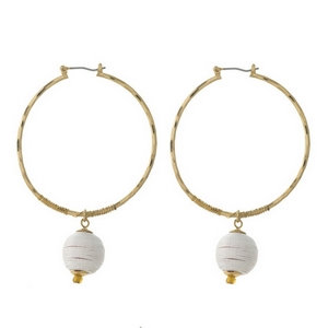 """Gold tone hoop earrings with a white thread wrapped bead. Approximately 2"""" in diameter."""