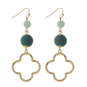 """Gold tone fishhook earrings with a green thread wrapped bead and an open clover shape. Approximately 3"""" in length."""