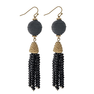 """Gold tone fishhook earrings with a black thread wrapped bead and a beaded tassel. Approximately 3"""" in length."""