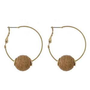 "Gold tone hoop earrings with a lever back and a beige thread wrapped bead. Approximately 1.5"" in diameter."