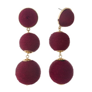 """Gold tone post style earrings with burgundy thread wrapped beads. Approximately 3"""" in length."""