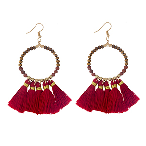 """Gold tone fishhook earrings with a natural stone beaded circle, accented with red thread tassels. Approximately 3"""" in length."""