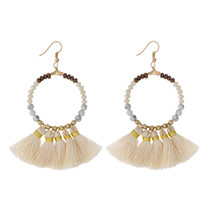 "Gold tone fishhook earrings with a natural stone beaded circle, accented with ivory thread tassels. Approximately 3"" in length."