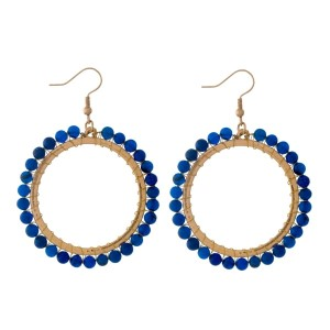 "Gold tone, open circle, fishhook earrings with wire wrapped blue natural stones. Approximately 2"" in diameter."