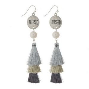"Fishhook earrings with a circle shape stamped with ""Blessed"" and a tiered metallic tassel. Approximately 3.5"" in length."