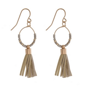 "Dainty gold tone fishhook earrings with an open circle shape and a faux leather tassel. Approximately 2"" in length."