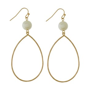 """Fishhook earrings with a hammered teardrop shape and a pearl bead. Approximately 3"""" in length."""