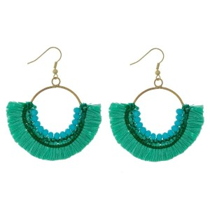 """Gold tone fishhook earrings with an open circle shape, fanned tassels and beaded accents. Approximately 2.25"""" in length."""