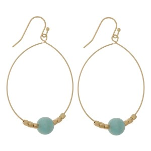 "Gold tone fishhook earrings with an oval shape and a natural stone bead. Approximately 2.25"" in length. Natural stone colors may vary."