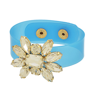 Blue PVC snap bracelet featuring a crystal clear rhinestone floral focal accented with gold tone snaps.