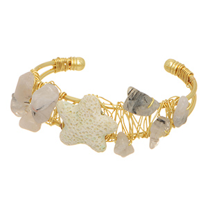 Gold tone cuff bracelet featuring clear wire wrapped stones with an ivory lava stone starfish focal.