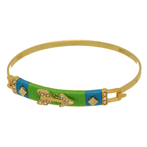 Gold tone bangle bracelet featuring a bar wrapped with blue and green thread and a rhinestone arrow focal.