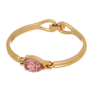 Matte gold tone bangle bracelet featuring a pink teardrop shaped rhinestone focal. Back clasp closure.