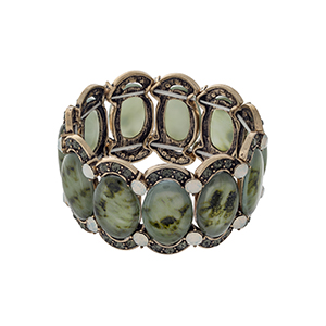 Burnished gold tone stretch bracelet displaying green oval shaped stones with black diamond and white opal rhinestone accents.